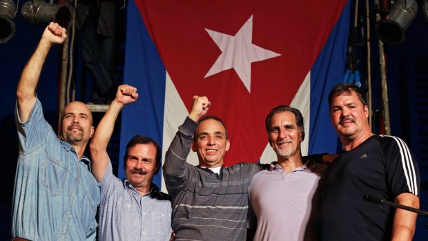 The Cuban Five. Three of them have their hands in the air in a socialist salute. They are all smiling. Behind them is the flag of Cuba.
